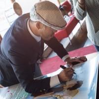 Ohjaaja Hiromasa Yonebayashi signeeraa julisteita Studio Ghibli -faneille. Kuva: Mari Mur