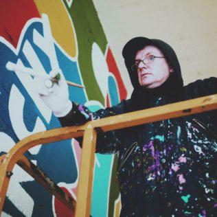 Thierry Noir restauroi Love & Anarchy -teosta. Kuva Sara Tamminen.